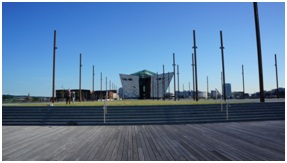 Titanic Belfast as seen from the far end of the slipways where RMS Olympic and RMS Titanic were built.  The original offices of Harland and Wolff can be seen on the left side of the museum.